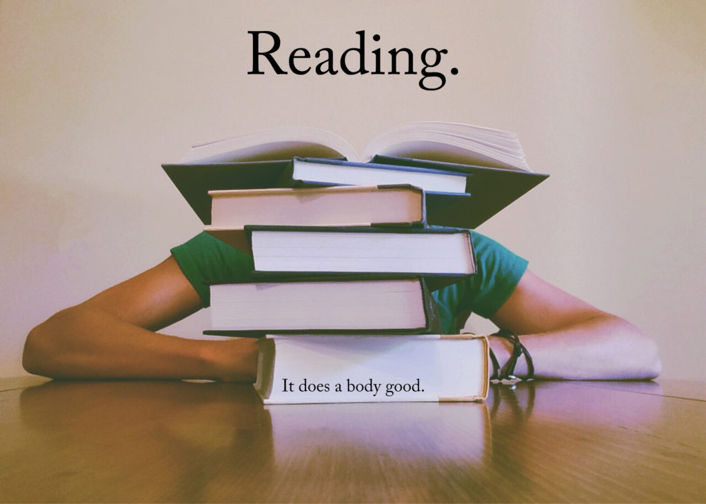 Photo of a person sitting at a table behind a pile of books. The top book is open. The overlaid text reads: Reading. It does a body good.