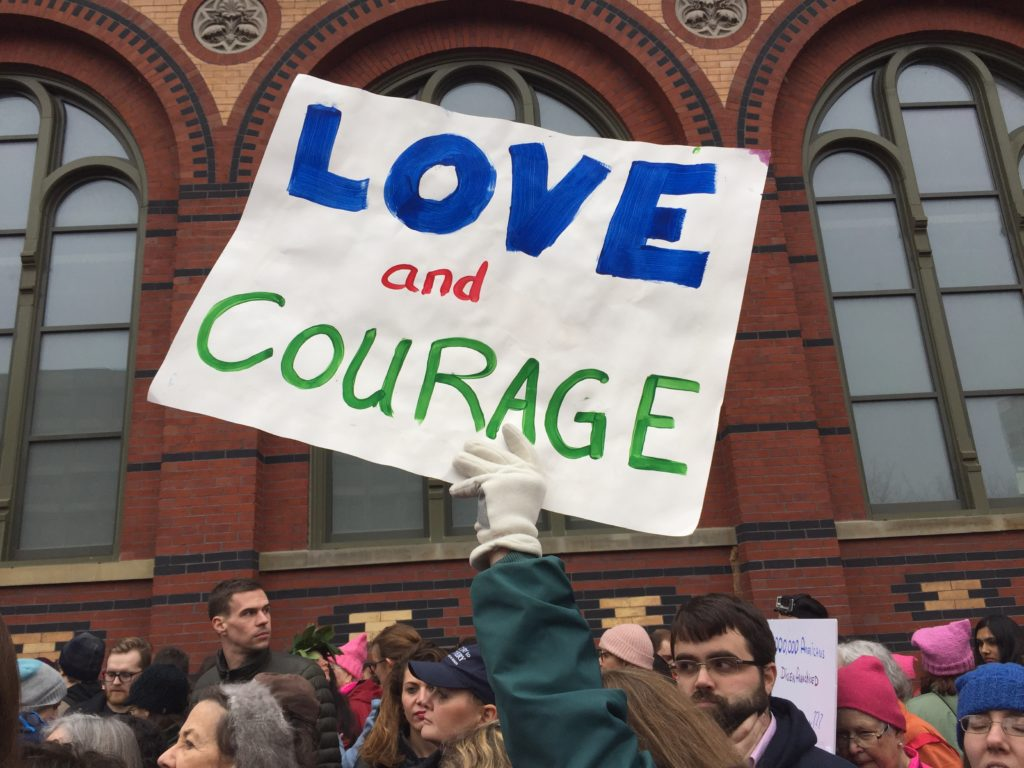 Protester holding a sign with the text Love and Courage
