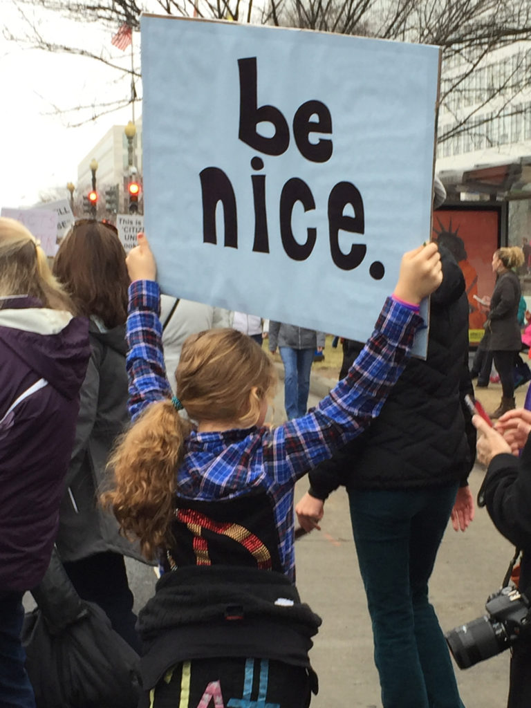 Young girl holding a sign saying Be Nice